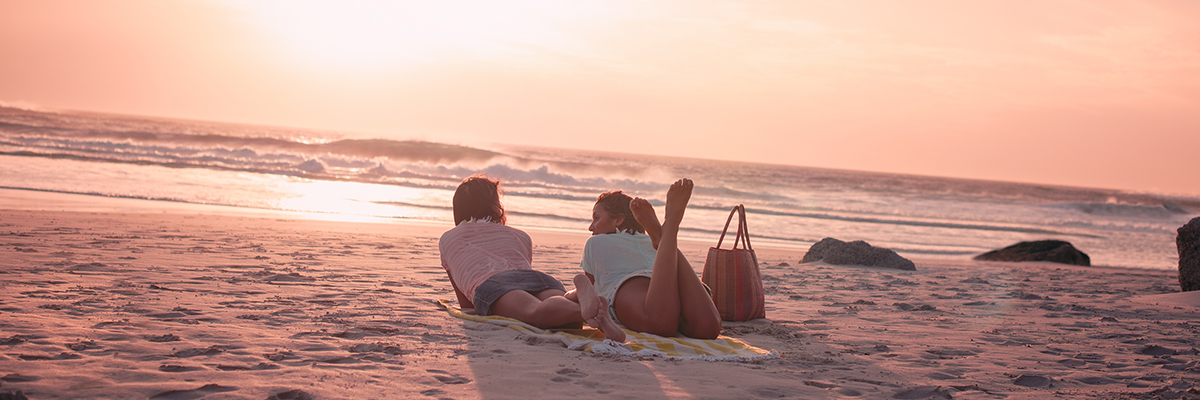 Two women laying on the beach at sunset